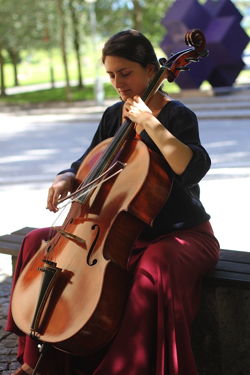 Leonor Palazzo playing the cello on a bench